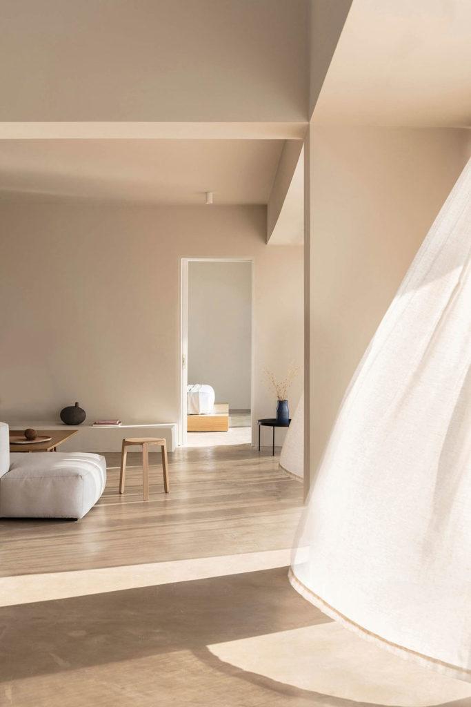 Interior de vivienda minimalista con paredes lisas de color crema, suelo de microcemento, muebles de diseño, cortinas blancas movidas por el viento que entra por las ventanas. Poppyns Magazine