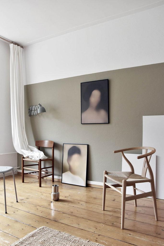 Habitación con suelo de madera, zócalo de color verde alto, techo blanco, sillas de madera, una alfombra blanca, una cortina blanca, un flexo y dos láminas con rostros difuminados. Poppyns Magazine