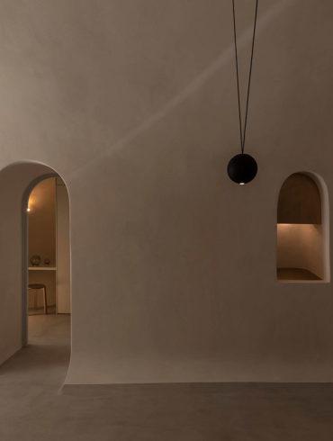 Interior de vivienda minimalista con paredes lisas en tono crema y suelo de microcemento, con una ventana y una puerta con arco ovalado. Poppyns Magazine
