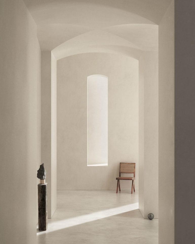 Pasillo de paredes blancas, bóveda de crucería y suelo de mármol con una escultura sobre un pilar de madera y una silla de madera y mimbre al fondo. Poppyns Magazine