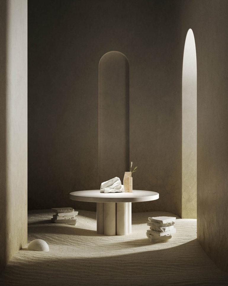Mesa de mármol circular con sillas hechas a base de trozos de mármol superpuestos, en una estancia con paredes lisas y suelo de arena. Poppyns Magazine