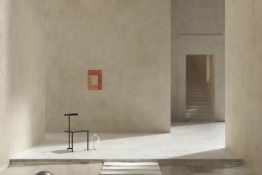 Interior de edificio con paredes de piedra lisas, un cuadro rojo sobre una pared, una puerta al fondo con unas escaleras ascendentes, una silla de forja junto a un jarrón de cristal y una piscina de agua clara con escalera de obra. Poppyns Magazine