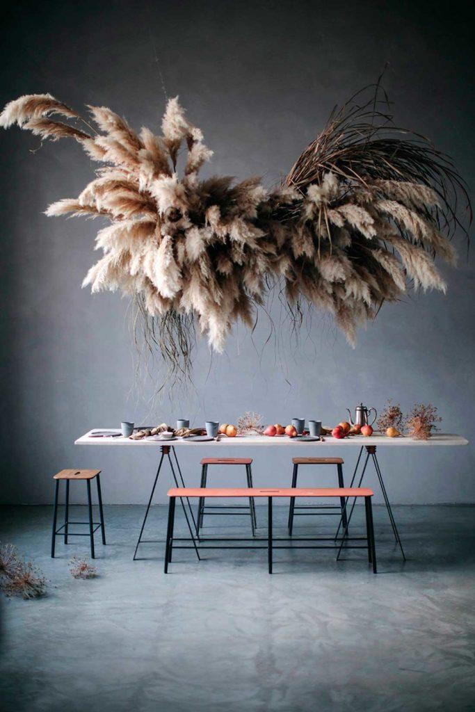 Planta abstracta a base de juncos y plumeros de color marrón y blanco suspendidos del techo sobre una mesa de mármol blanco con caballetes finos de hierro, taburetes y bancos de madera y platos, vajilla y fruta sobre la mesa. Poppyns Magazine