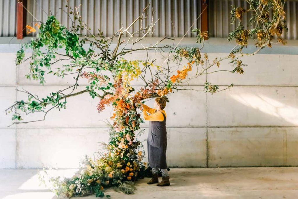 Mujer con un peto azul, camiseta naranja, botas y dos coletas podando un árbol de flores y plantas de colores verde, amarillo, marrón y naranja. Poppyns Magazine