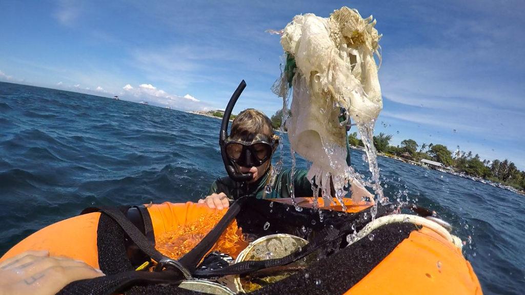 Buzo sacando plástico del fondo del océano. Poppyns Magazine