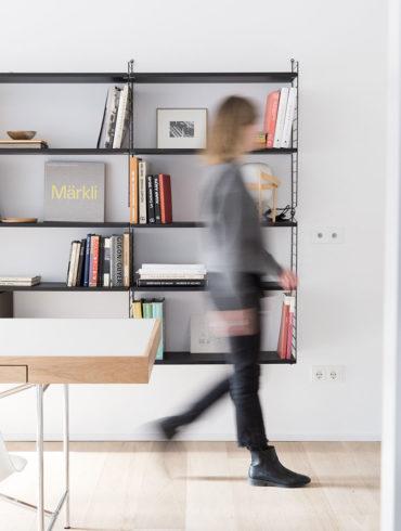 Mujer difuminada andando por un salón con una estantería de diseño con libros, una mesa de madera y suelo de parquet. Poppyns Magazine