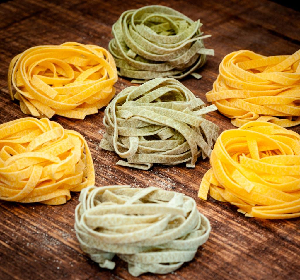 Pasta integral de color amarillo y verde sobre una mesa de madera. Poppyns Magazine