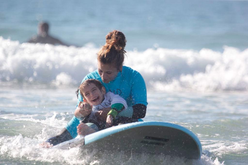 Una chica abrazando a un niño sonriendo sentados en una tabla de surf dentro del mar. Poppyns Magazine