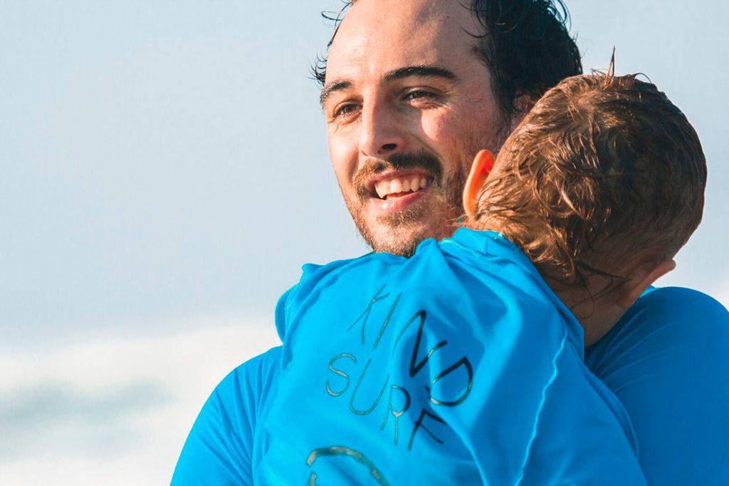 """Un chico sonriendo abrazando a un niño con una camiseta azul que pone """"kind surf"""". Poppyns Magazine"""