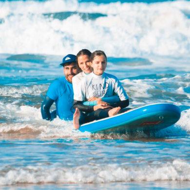"""Tres personas, un chico con gorra, una chica y una niña con una camiseta que pone """"kind surf"""", sentadas encima de una tabla de surf dentro del mar. Poppyns Magazine"""