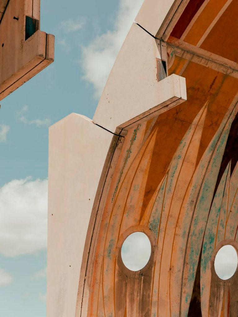 Detalle de edificio arquitectónico con estructura curva y ventanales circulares en fachada a modo de camarotes. Poppyns Magazine