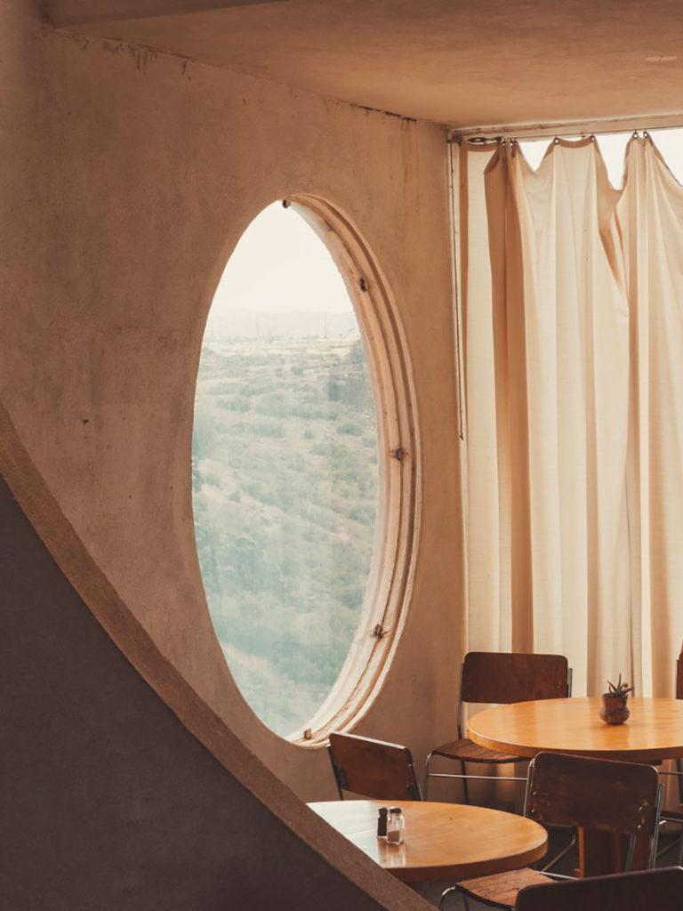 Habitación interior minimalista con un ventanal circular acristalado en una pared de hormigón, unas mesas de madera y sillas de diseño. Poppyns Magazine