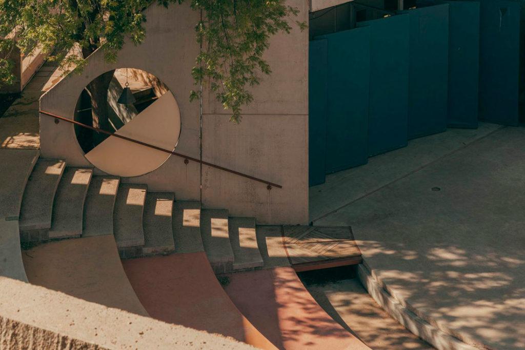Escalera junto a una grada semicircular en madera y una pared de hormigón con una circunferencia troquelada. Poppyns Magazine
