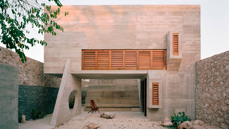 Edificio arquitectónico de hormigón y madera con formas geométricas, ventanales de madera con mallorquinas y zona ajardinada. Poppyns Magazine