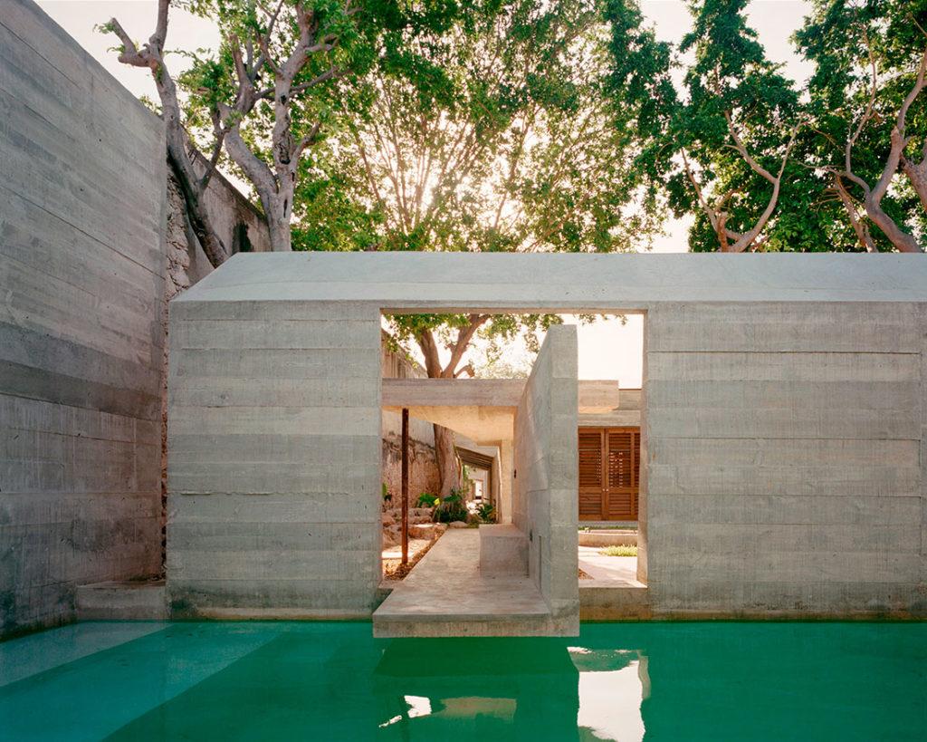 Estructura de hormigón junto con una piscina con agua transparente, vegetación y ventanales de madera con mallorquinas. Poppyns Magazine