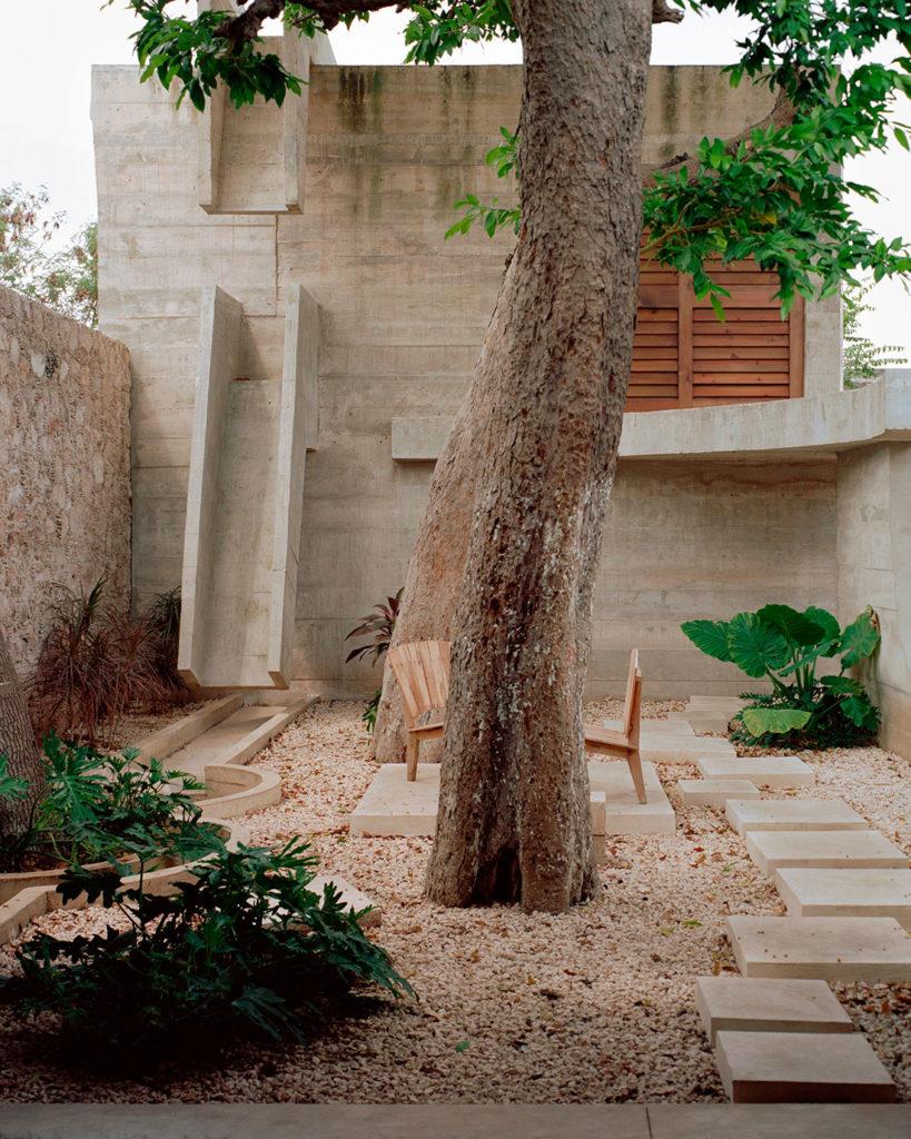 Jardín exterior de un edificio arquitectónico con forma de cubo de hormigón, con una árbol en el centro, suelo empedrado, vegetación y sillas de madera. Poppyns Magazine