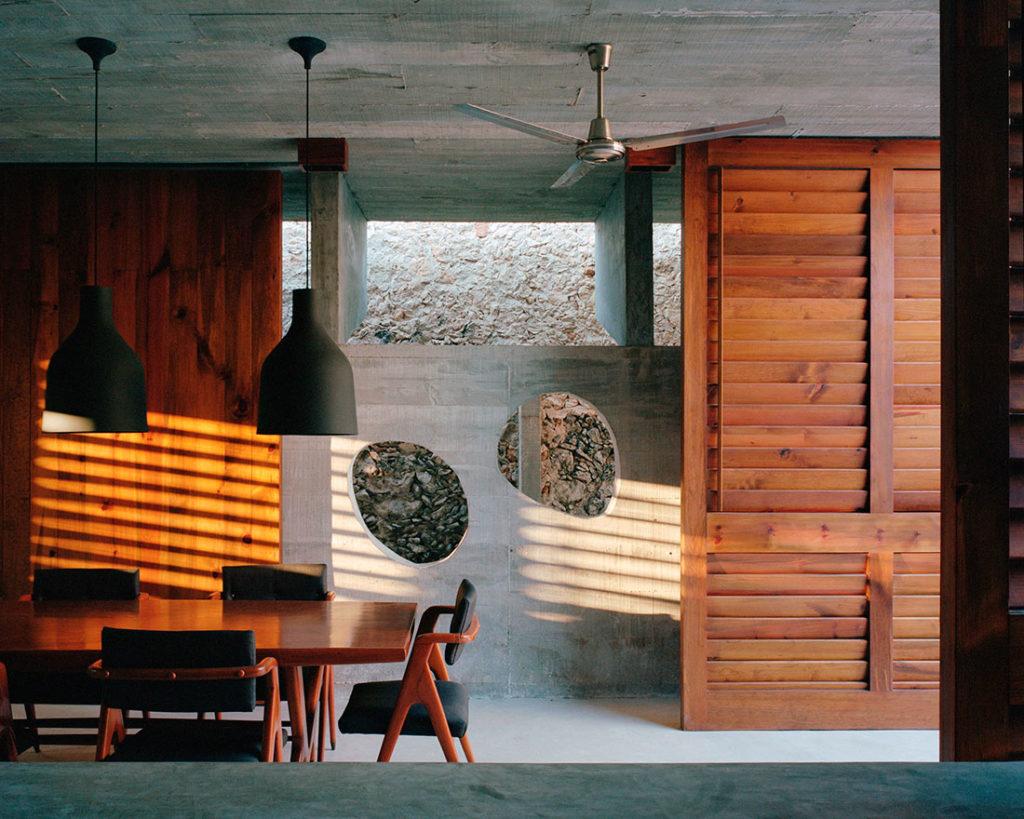 Comedor de hormigón y madera con una mesa y sillas de diseño de madera, dos lámparas colgadas del techo, un ventilador y un ventanal de madera con menorquinas. Poppyns Magazine