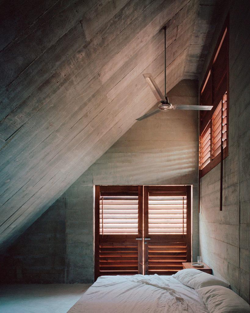 Dormitorio abuardillado de hormigón con una cama deshecha y una ventana con mallorquinas de madera y un ventilador colgado del techo. Poppyns Magazine