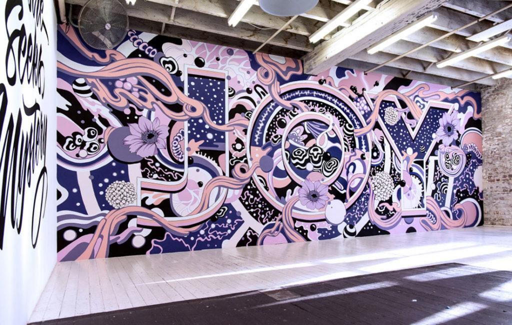 Mural ilustrado con motivos florales y letras con la palabra JOY. Poppyns Magazine