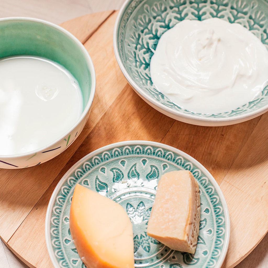 Juego de tres bowls con motivos decorativos verdes con diferentes ingredientes, queso, nata y leche. Todo ello sobre una superficie de madera. Poppyns Magazine
