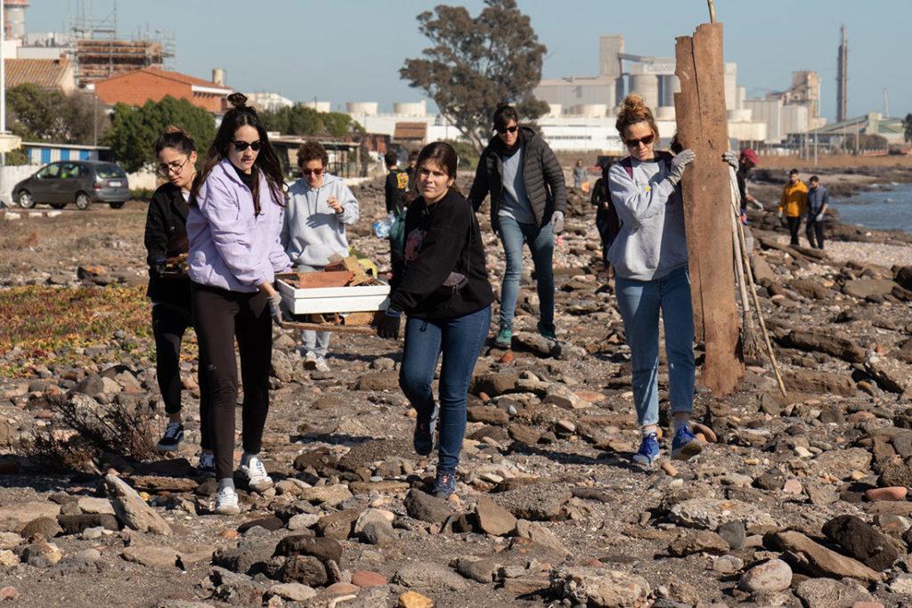 Grupo de mujeres cargando con restos de madera y ladrillos andando en una playa de roca y arena. Poppyns Magazine