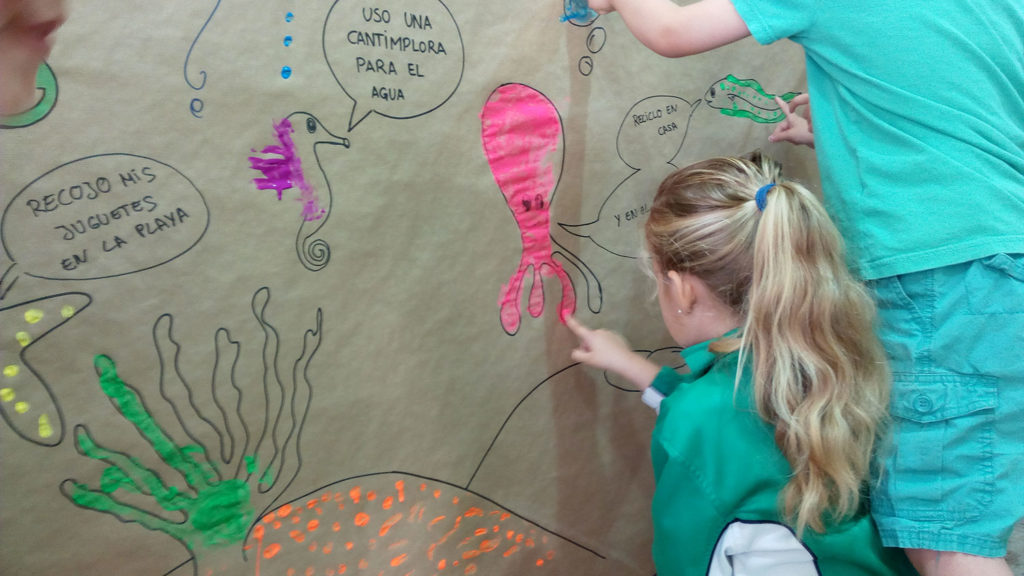 Niña rubia con coleta de espaldas dibujando un pulpo rosa sobre un mural con un caballo de mar, algas y estrellas de mar, donde está escrito 'recojo mis juguetes en la playa', 'uso una cantimplora para el agua'. Poppyns Magazine