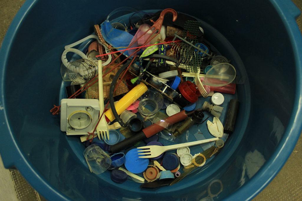 Cubo de plástico lleno de restos plásticos como tapones, enchufes, cubiertos, etc. Poppyns Magazine