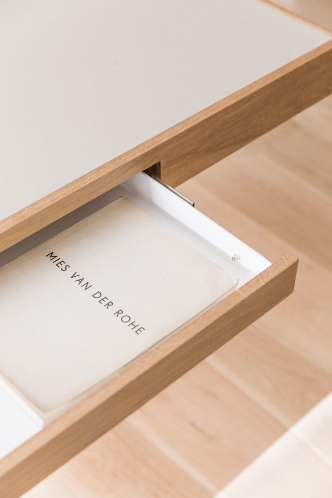 Detalle de un mueble de madera con cajonera abierta y un libro dentro con título en la portada 'Mies Van Der Rohe'. Poppyns Magazine