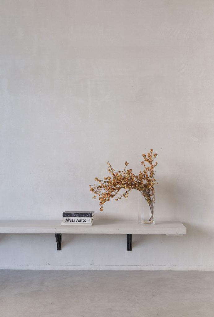 Banco de madera lacada en blanco anclado a una pared blanca por unas escuadras negras, con libros apilados (entre ellos Alvar Aalto) y un búcaro de cristal con una planta de hoja ocre. Poppyns Magazine