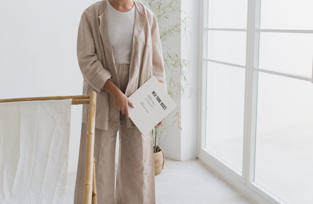 Persona sujetando una revista con portada blanca y con texto 'New York Rises', vestida con pantalón ancho, camiseta blanca y chaqueta tres cuartos en una habitación blanca con un ventanal. Poppyns Magazine
