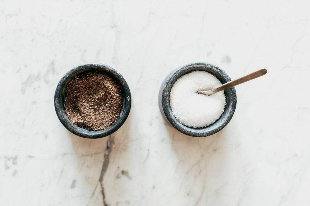 Dos tarros de cerámica con azucarero de azúcar moreno y azúcar blanco con una cuchara, ambos sobre una superficie de mármol blanco. Poppyns Magazine