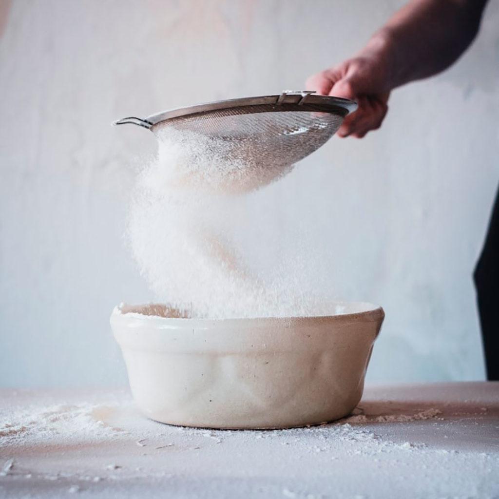 Persona colando azúcar blanco con un colador sobre un recipiente de cerámica blanco. Poppyns Magazine