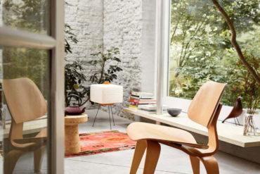 Silla de Eames de madera en una habitación con paredes de ladrillo pintado de blanco, suelo de cemento, una alfombras en tonos rojizos, libros, vegetación y un gran ventanal con un jardín de fondo. Poppyns Magazine
