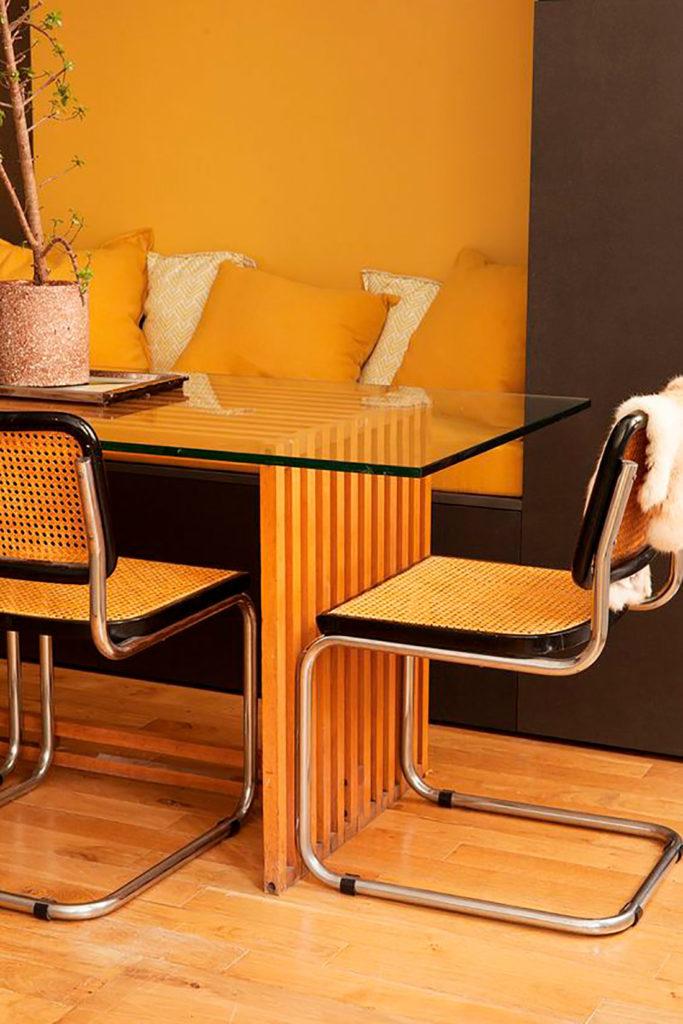 Sillas de Marcel Breuer de mimbre con estructura tubular en torno a una mesa de estructura de madera y superficie de cristal sobre suelo de parquet. Poppyns Magazine