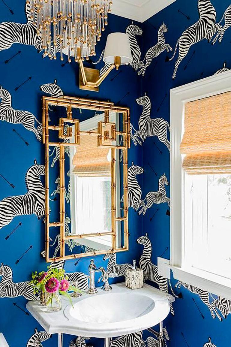 Cuarto de baño empapelado con papel de color azul marino con cebras y flechas dibujadas, una pila blanca de estilo retro, unas flores, una ventana de madera con estor de mimbre. Poppyns Magazine