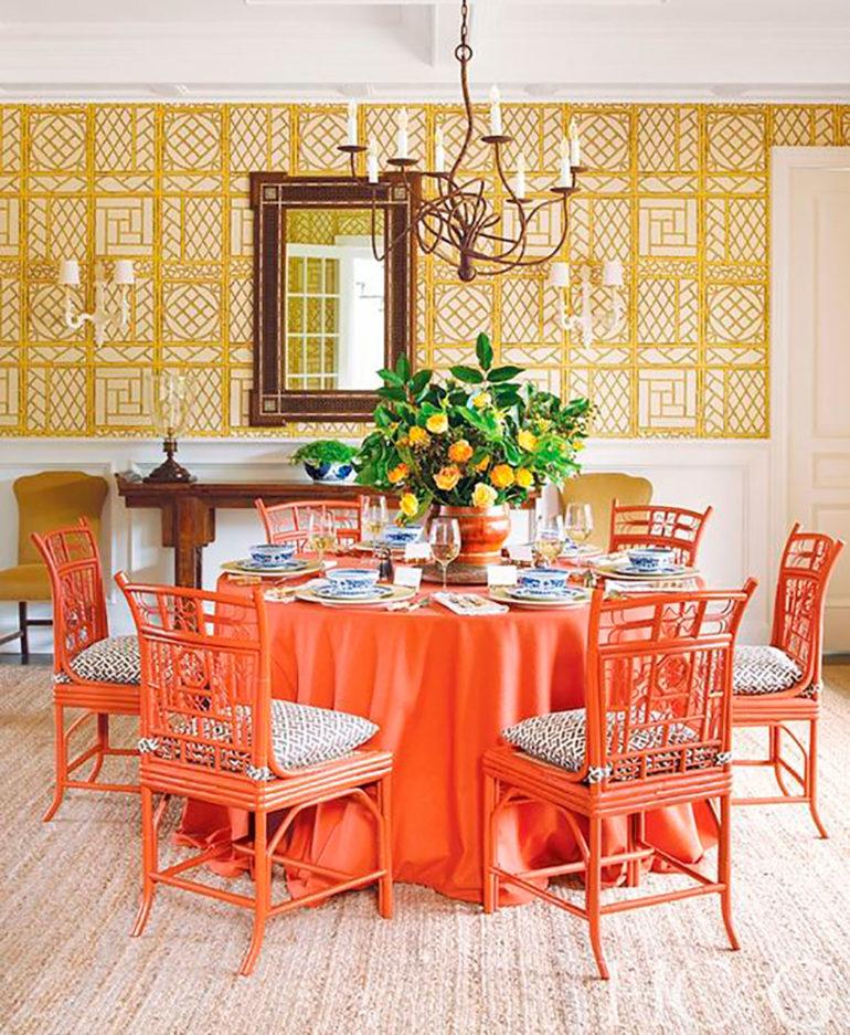 Comedor con una mesa redonda con mantel rojo sobre una alfombra, sillas de madera lacadas en rojo, cojines de colores, vajilla con elementos decorativos, un centro de flores y una boiserie en la pared con ornamentos dorados decorativos y un espejo en el centro. Poppyns Magazine