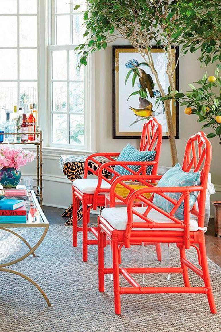 Salón con butacas en madera tintada en rojo, cojines de colores, una alfombra, un ventanal con carpintería de madera lacada en blanco, un naranjo, un cuadro con pájaros de colores, un minibar y una mesa de cristal con perfiles metálicos sobre una alfombra a rombos. Poppyns Magazine