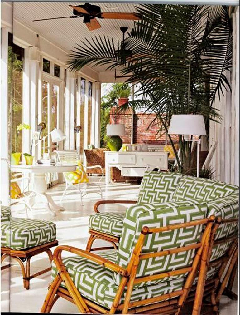 Salon acristalado con carpintería de madera lacada en blanco, mobiliario de madera lacada en blanco, vegetación y sillones de madera con cojines estampados en verde. Poppyns Magazine