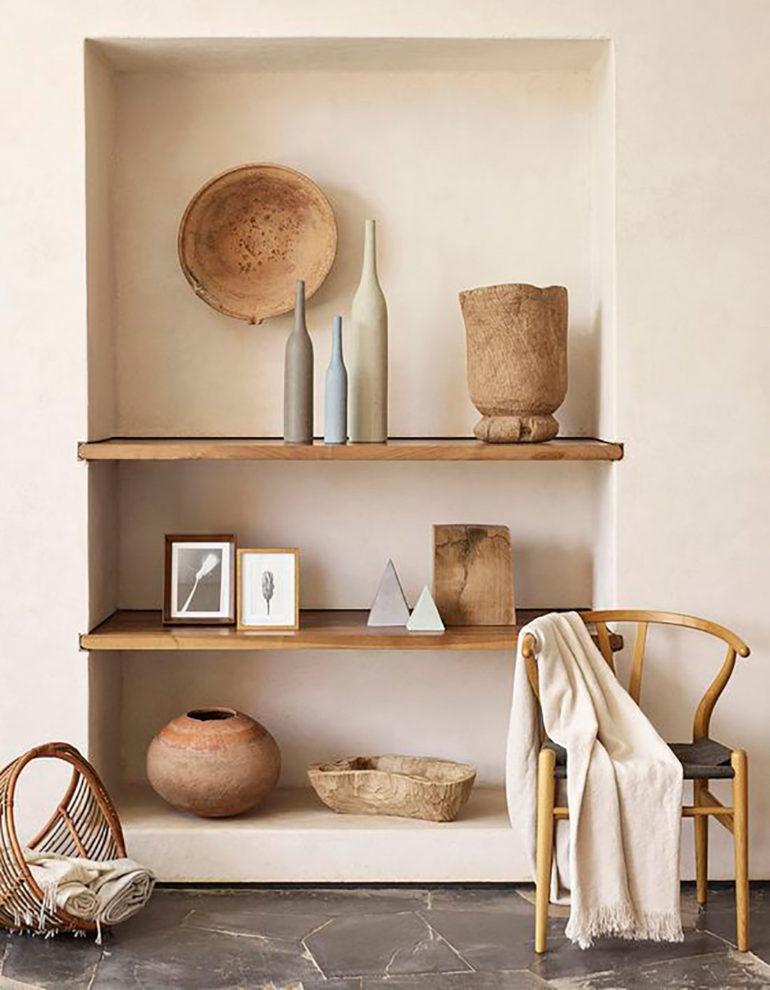 Estantería de obra con baldas de madera y objetos decorativos de madera y barro junto con mobiliario de madera y suelo de mármol. Poppyns Magazine
