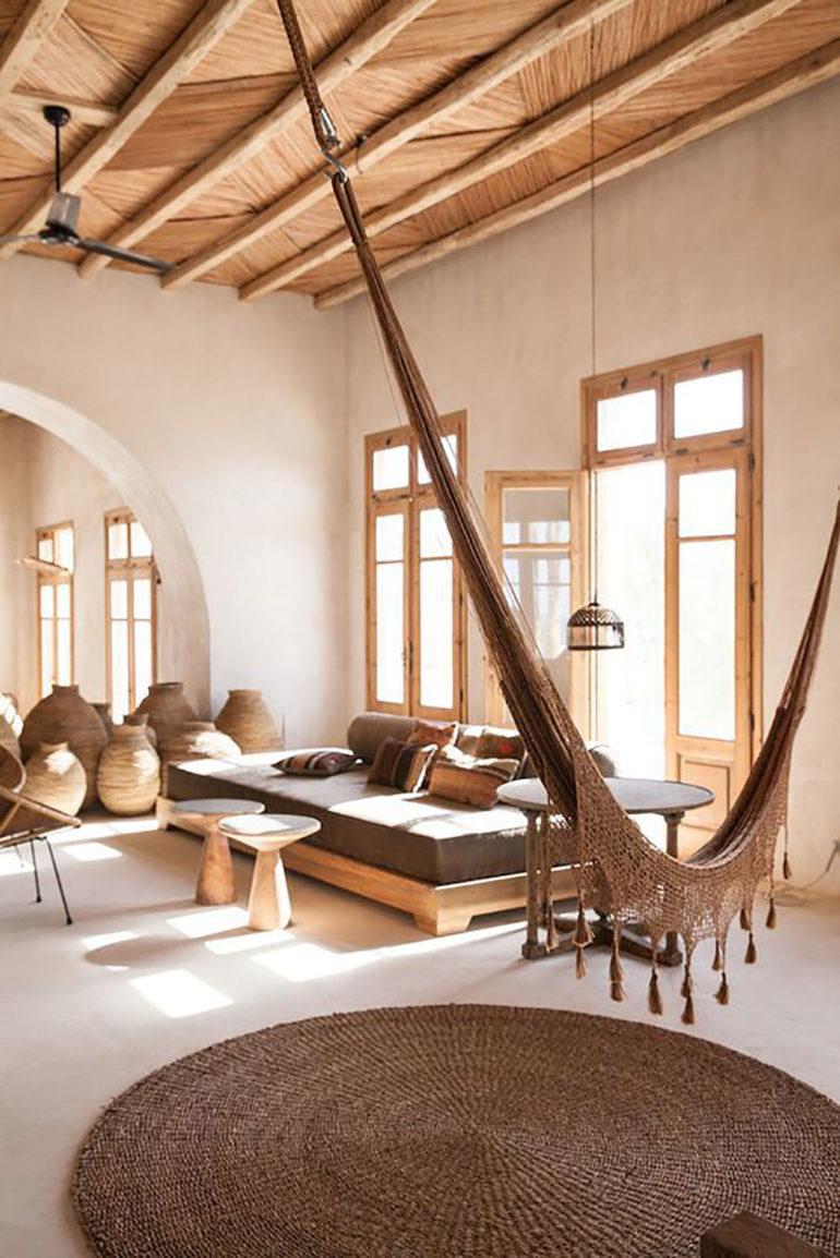 Salón con suelo y paredes de cemento blanco, carpinterías de madera, tinajas, techo de madera, mobiliario de madera, una alfombra de mimbre tintado y una hamaca colgada del techo. Poppyns Magazine