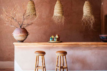 Habitación con taburetes de madera en una barra de madera, con suelo de ladrillo rojo, lámparas de mimbre y techo de troncos de madera y cañizo. Poppyns Magazine