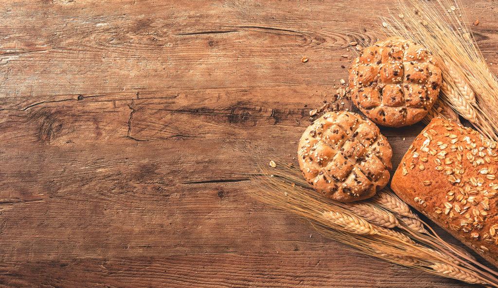 Hogaza de pan con semillas de trigo y sésamo junto a espigas de trigo sobre una mesa de madera. Poppyns Magazine