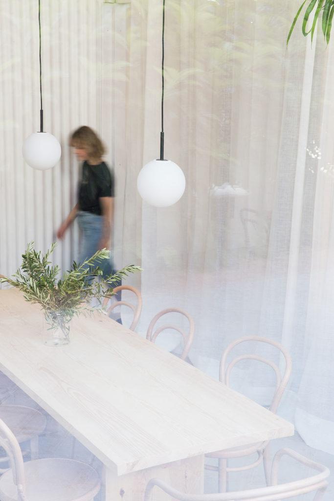 Mujer rubia andando junto a una mesa larga de madera con sillas de madera, un centro verde, dos lámparas colgantes y cortinas blancas. Poppyns Magazine