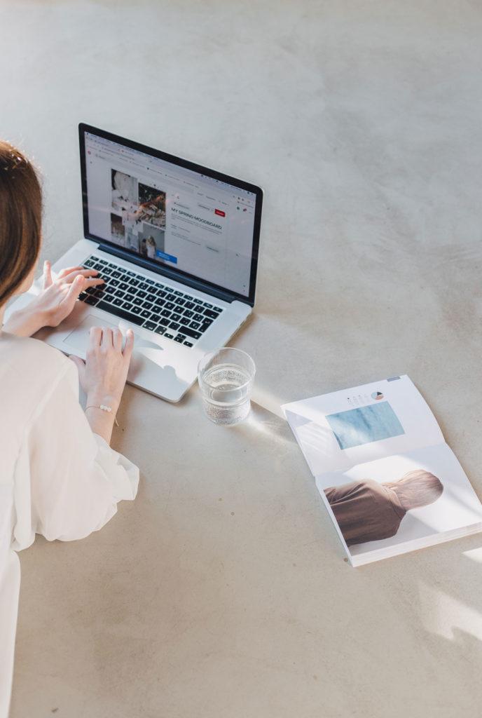 Mujer rubia tumbada en un suelo de cemento pulido con las manos sobre el teclado de un portátil, junto con un vaso con agua y una revista abierta. Poppyns Magazine
