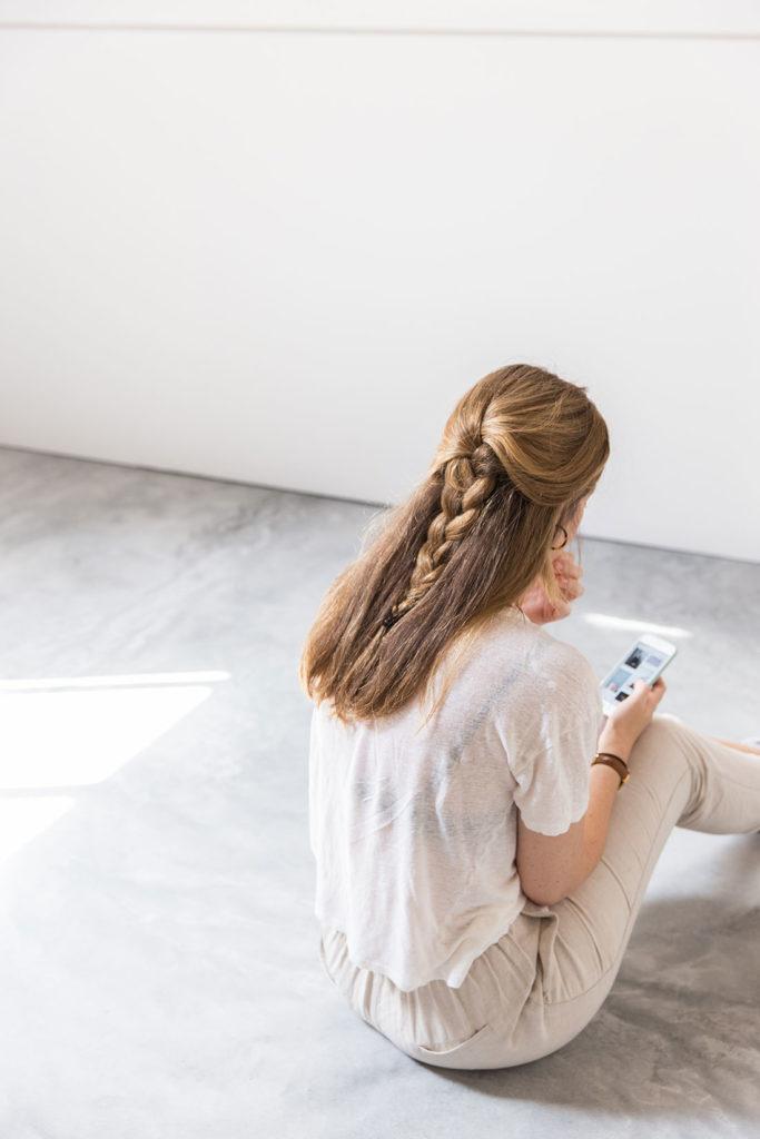 Mujer rubia de pelo largo con una trenza, sentada en un suelo de cemento pulido mirando el móvil. Poppyns Magazine