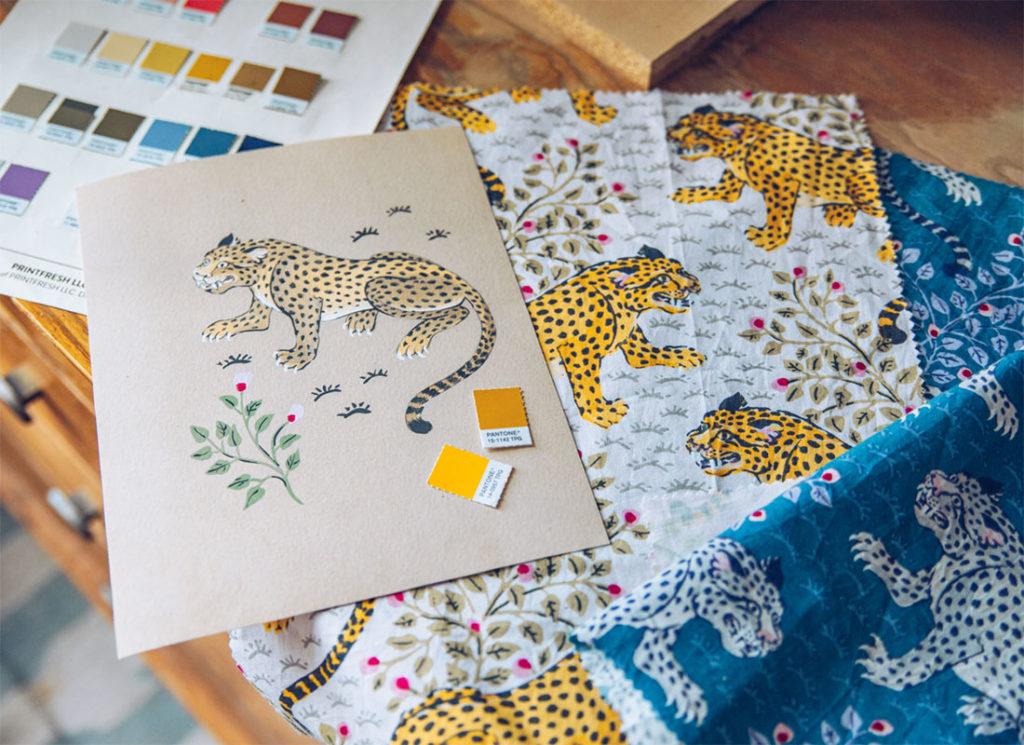 Patrón de un leopardo ilustrado en un cartón con dos tonos de pantone amarillo y ocre, y una pantonera al fondo y dos telas blanca y azul con el patrón del leopardo estampado. Poppyns Magazine