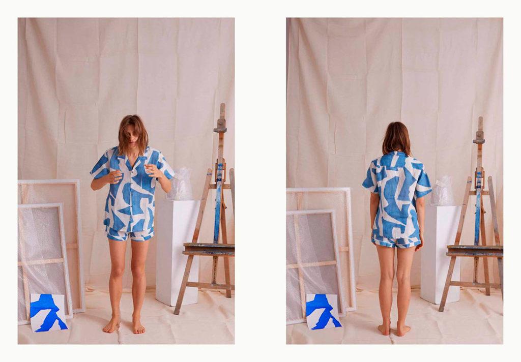 Mujer rubia en un estudio de fotografía con lienzos y un caballete fotografiándose de frente y de espaldas con un conjunto de pantalón corto y camisa de manga corta blanco con estampados azules. Poppyns Magazine