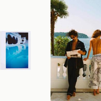Hombre moreno con pijama largo y parte de arriba abierta leyendo el periódico Le Monde con gafas de sol, y mujer de espaldas con pantalón blanco estampado con leopardos con la parte de arriba desnuda asomada a una barandilla blanca mirando el mar. Poppyns Magazine