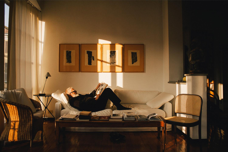 hombre mayor leyendo tumbado en un sofá de un salón al atardecer