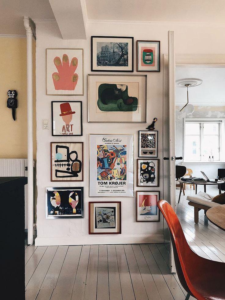 pared con láminas de arte enmarcadas con diferentes marcos creando un mosaico en un salón grande